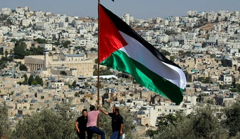 Demonstrators place a Palestinian flag during a protest against the planned visit of Israeli Prime Minister Benjamin Netanyahu, Hebron, West Bank, September 4, 2019.