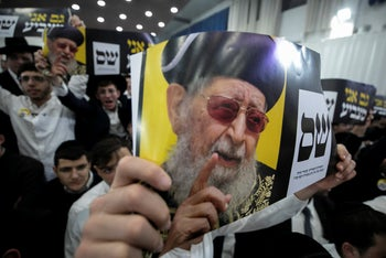 Shas supporters in Jerusalem holding up images of the party's spiritual leader, the late Rabbi Ovadia Yosef, April 9, 2019.
