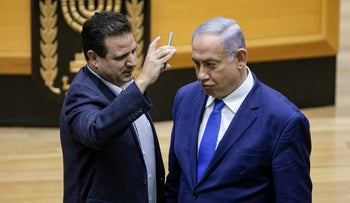 Joint List Chairman Ayman Odeh films Netanyahu with his phone camera during the Knesset discussion on the Likud's cameras bill, September 11, 2019.