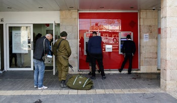 Israelis draw money from an ATM in Beit Shemesh, December 12, 2016.
