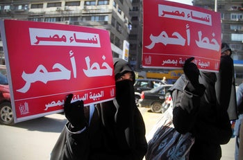 File photo: Two women hold up banners in Arabic that read, 'Egyptian women, red line,' during a rally supporting women's right in Cairo, Egypt, December 27, 2011.