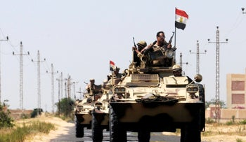 Soldiers in military vehicles proceed towards the al-Jura district in El-Arish city, Egypt May 21, 2013.