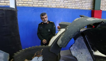 Head of the Revolutionary Guard's aerospace division Gen. Amir Ali Hajizadeh looks at debris from what the division described as a U.S. drone shot down on Thursday, in Tehran, Iran, on June 21, 2019.