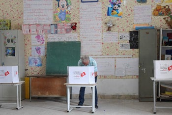A Tunisian voter fills his ballot at a polling station near the capital Tunis, on September 15, 2019.