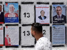 A Tunisian man walks in front of posters of presidential candidates in the capital Tunis, on September 7, 2019.