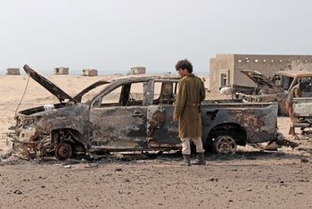 A Yemeni southern separatist fighter inspects wreckage.
