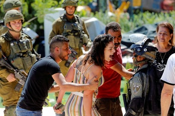 A Palestinian woman argues with an Israeli border policewoman over the Israeli demolition of a building, in Beit Jala in the Israeli-occupied West Bank, August 26, 2019.