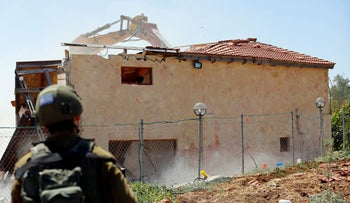 An Israeli machinery demolishes a Palestinian building housing an apartment and a restaurant in Beit Jala in the Israeli-occupied West Bank on August 26, 2019.