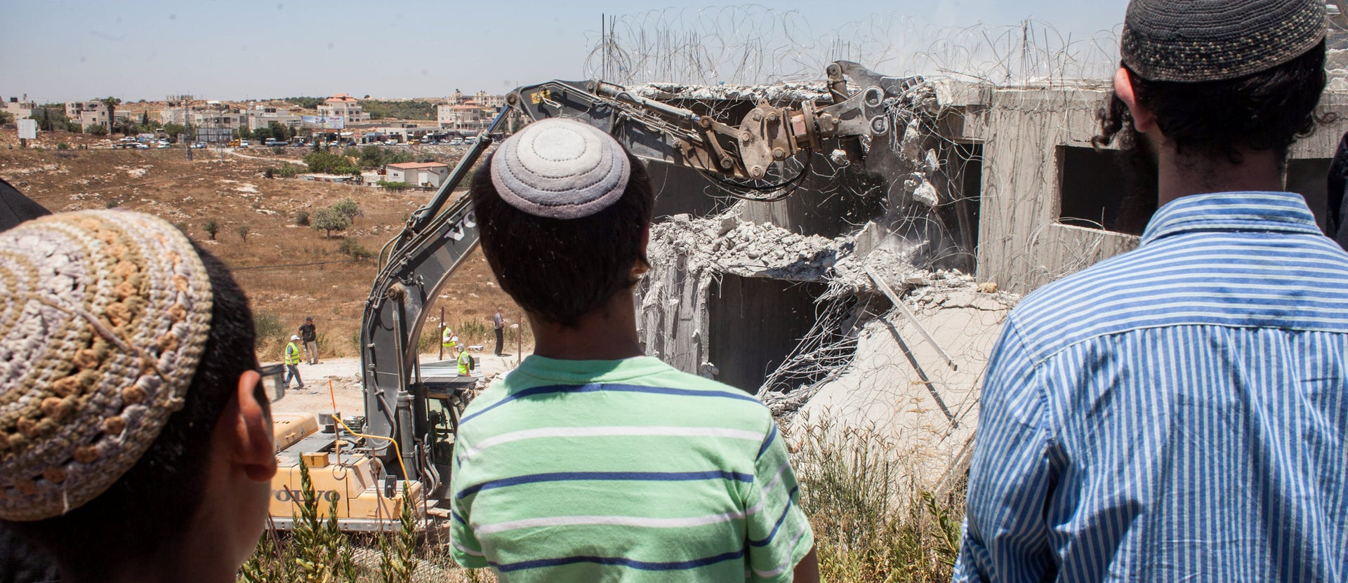 Jewish settlers watch as Israeli forces demolish an illegally built structure in a West Bank settlement