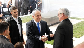Prime Minister Benjamin Netanyahu and Kahol Lavan leader Benny Gantz shake hands at a memorial service for Shimon Peres, September 19, 2019.