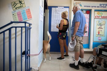 Voters (and a curious dog) waiting in line to vote at a polling station in Ramat Aviv on Election Day, September 17, 2019.