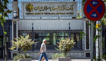 A man walks past the central bank of Iran in Tehran, Iran, August 1, 2019.