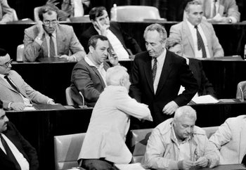 After Israel's then-Prime Minister Shimon Peres addressed the Knesset on peace talks with Jordan, Ariel Sharon (who opposed them) studiously plays with a piece of paper rather than congratulating him. Oct. 28, 1985
