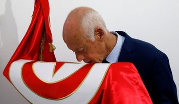 Presidential candidate Kais Saied kisses a Tunisian flag after unofficial results announced during the Tunisian presidential election in Tunis.
