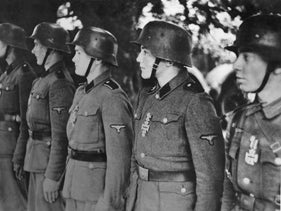 """File photo: Members of the 12th SS Panzer Division """"Hitler Youth"""" line up to receive an award, July 1944."""