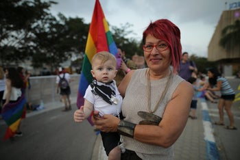 A woman with her child attend Be'er Sheva's Pride Parade, 2018.
