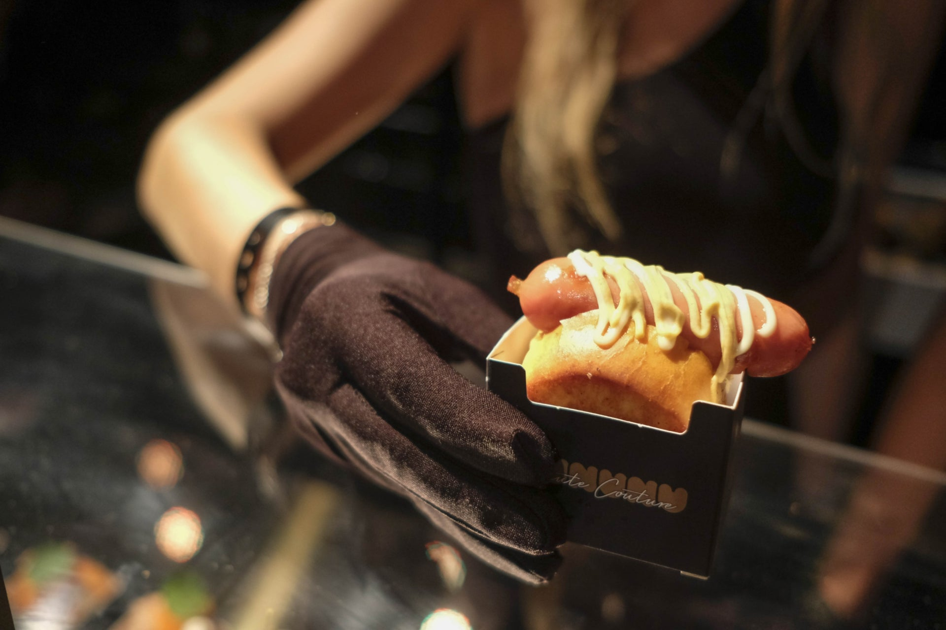A guest is holding a hot dog served in a branded box with Raidman's name on it.