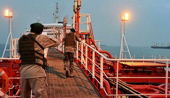 Two armed members of Iran's Revolutionary Guard inspect the British-flagged oil tanker Stena Impero, which was seized in the Strait of Hormuz, in the Iranian port of Bandar Abbas, July 21, 2019.