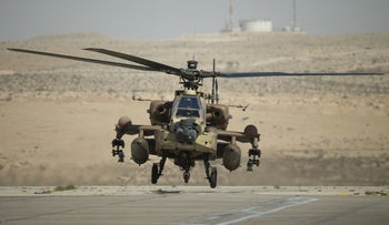 An Israeli AH-64 Apache helicopter lands during a display for foreign media at the Ramon air force base in southern Israel, October 21, 2013.