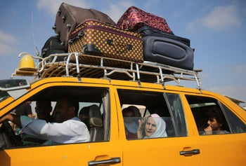 Palestinians ride in a car as they wait at the Rafah crossing to Egypt in the southern Gaza Strip, August 25, 2014.