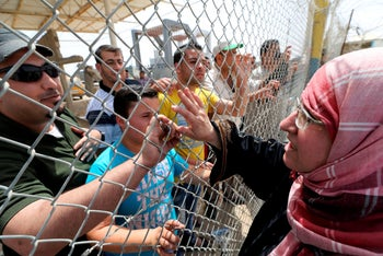 A Palestinian woman waves to her relatives standing behind a fence upon her return to Gaza through Rafah border crossing between Egypt and southern Gaza Strip May 27, 2015.