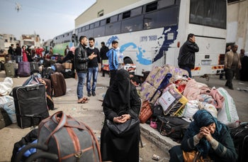 Palestinians gather as they wait to get permits to travel through the Rafah border crossing with Egypt, in Khan Younis, Southern Gaza strip, 18 November 2017.