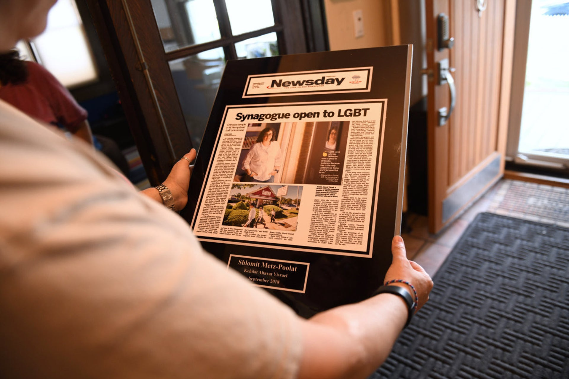 Shlomit Metz-Poolat holding a framed copy of a newspaper story about the opening of Kehilat Ahavat Yisrael in West Hempstead.