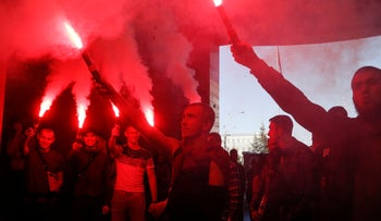 Activists from the ultranationalist, anti-Semitic National Corps light flares during a rally at the appeals court in Kiev, Ukraine. Sept. 5, 2019