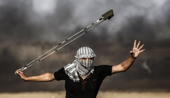 A Palestinian protester uses a slingshot to throw rocks during clashes with Israeli forces following a demonstration along the border with Israel in the southern Gaza strip, September 27, 2019.