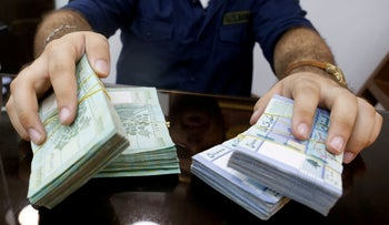 FILE PHOTO: A money exchange vendor displays Lebanese pound banknotes at his shop in Beirut, Lebanon, August 16, 2018.