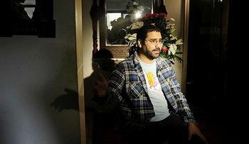 Egyptian blogger and activist Alaa Abdel Fattah speaks during a TV interview at his house in Cairo on December 26, 2011.
