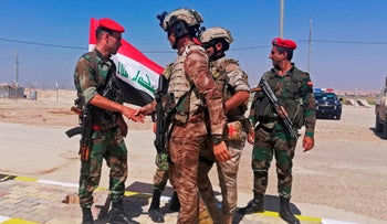 Iraq and Syria border guards congratulate each other during the opening ceremony of the crossing between the Iraqi town of Qaim and Syria's Boukamal, in Anbar province, Iraq, September 30, 2019.
