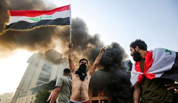 A protester waves an Iraqi flag during a demonstration against state corruption, failing public services and unemployment, Baghdad, October 1, 2019.
