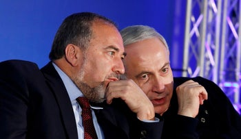 Benjamin Netanyahu (R) converses with Avigdor Lieberman during a Likud-Yisrael Beitenu campaign rally in the southern Israeli city of Ashdod, January 16, 2013