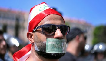 An anti-government protester has a Lebanese banknote taped over his mouth during a demonstration, in downtown Beirut, Lebanon, September 29, 2019