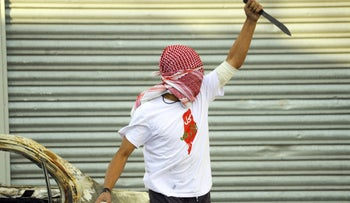 A Palestinian demonstrator in Jerusalem's Shoafat refugee camp raises a knife, in October 2015.