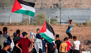 A young Palestinian protester uses a slingshot to hurl stones at Israeli forces across the border amidst clashes following a demonstration along the fence with Israel east of Gaza City on October 4, 2019.