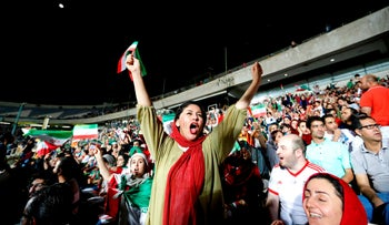 An Iranian woman cheers at a soccer match between Portugal and Iran at Azadi Stadium, June 25, 2018.
