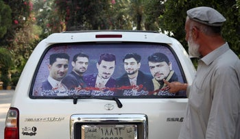 Mohammad Yaqoob Malikzada shows pictures of four brothers who were killed by Afghan soldiers, on October 1, 2019.