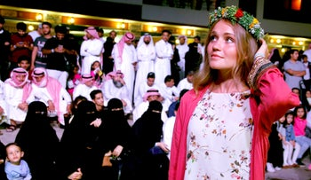 American vacationer Paris Verra wears a colorful crown native to the village of Rijal Almaa during the al-Soudah festival, in Abha, southwest Saudi Arabia, August 23, 2019.