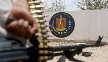 Yemeni government soldier holds a weapon in front of the headquarters of the separatist Southern Transitional Council in Ataq, Yemen, August 27, 2019
