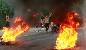 Anti-government protesters set fires and close a street during a demonstration in Baghdad, Iraq, Sunday, Oct. 6, 2019
