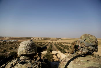 File photo: American troops look out toward the border with Turkey from a small outpost near the town of Manbij, northern Syria, February 2018.