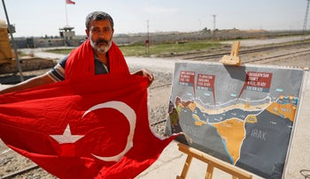 A man holds a Turkish flag as he stands next to a map showing Turkey's suggested operation in Syria, at the border between Turkey and Syria, southeastern Turkey, October 8, 2019.