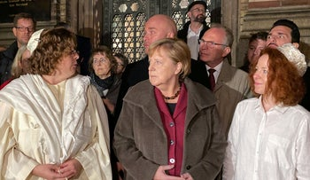 German Chancellor Angela Merkel (C) stands with Rabbi Gesa S. Ederberg (L) and other members of the Jewish community at a vigil outside the New Synagogue in Berlin on October 9, 2019