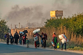 Civilians flee with their belongings amid Turkish bombardment on Syria's northeastern town of Ras al-Ain in the Hasakeh province along the Turkish border on October 9, 2019.