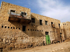 A Palestinian man looks out of an ancient building in the Bedouin village of Al-Maleh in Jordan valley in the West Bank March 13, 2019.