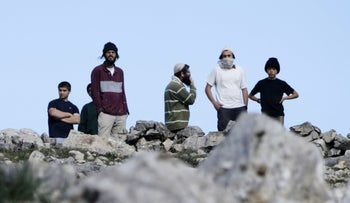 Israeli settlers of Yitzhar take position during a confrontation with Palestinians over an area in Burin village in the West Bank, January 14, 2014.