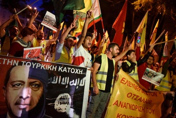 Kurds living in Athens protest near the Turkish embassy holding banners showing Turkish president Erdogan morphing into an ISIS fighter. October 9, 2019