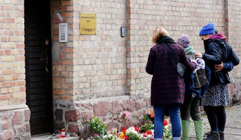 People mourn outside the synagogue in Halle, Germany October 10, 2019, after a far-right shooter tried and failed to enter, then killed two people nearby